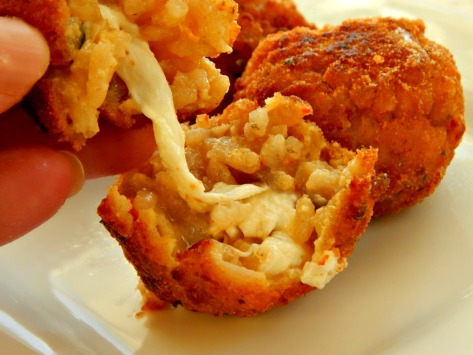 Arancini - breaded & fried risotto balls stuffed with Mozzarella cheese.